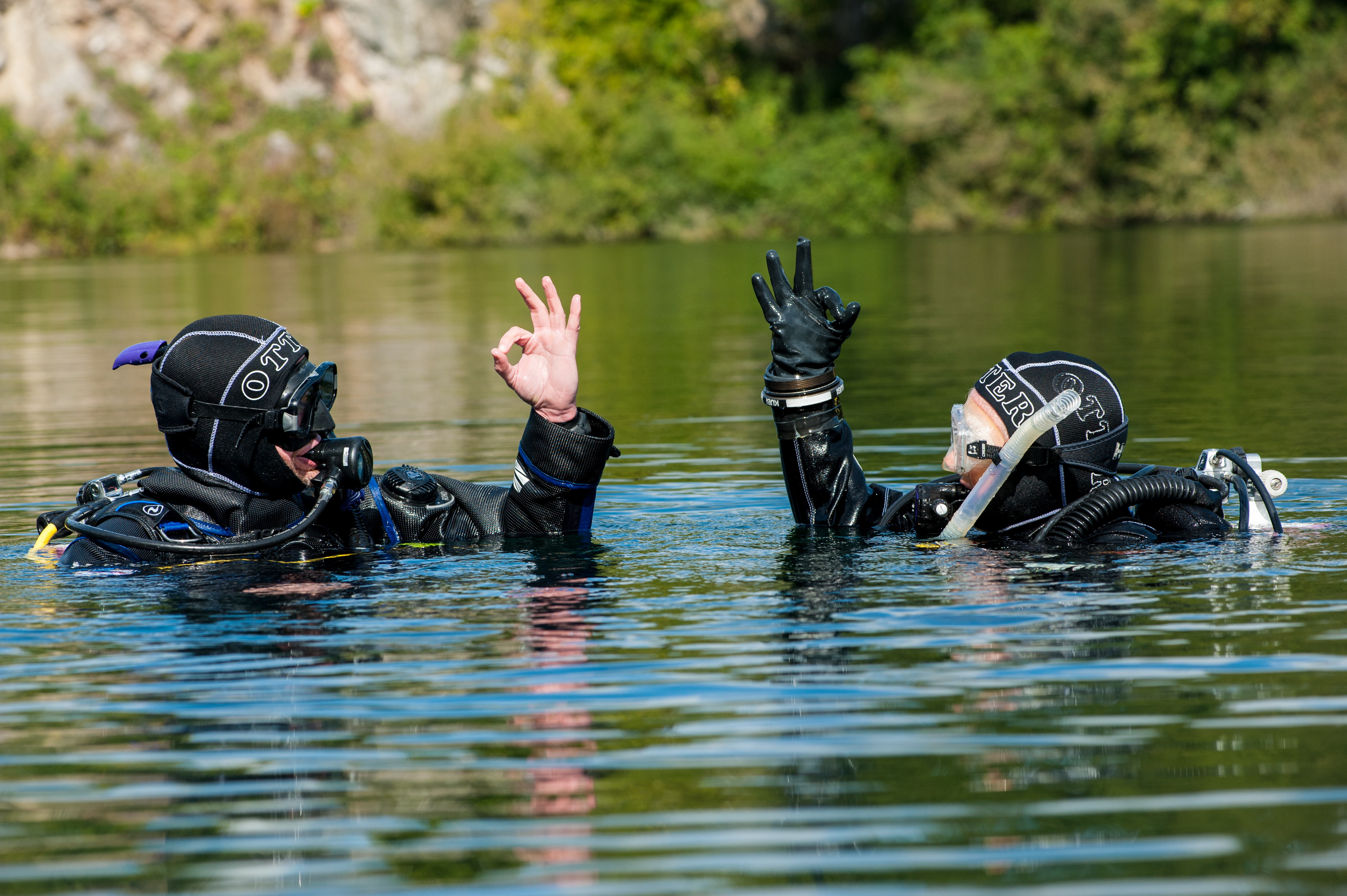 Divers in Water Using Hand Signal